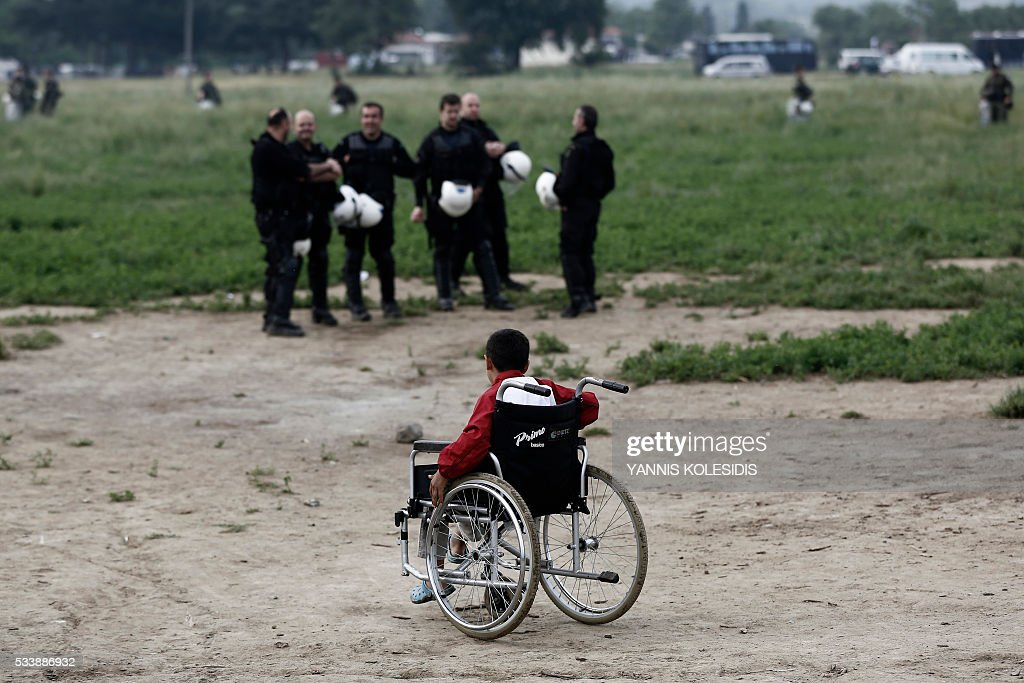 A boy on a wheelchair looks at riot police officers during an evacuation operation by Greek police forces of the makeshift camp at the Greek-Macedonian border, near the village of Idomeni, on May 24, 2016. In an operation which began shortly after sunrise on May 24, hundreds of Greek police began evacuating the sprawling camp which is currently home to 8,400 refugees and migrants, among them many families with children, an AFP correspondent said. At its height, there were more than 12,000 people crammed into the site, many of them fleeing war, persecution and poverty in the Middle East and Asia, with the camp exploding in size since Balkan states began closing their borders in mid February in a bid to stem the human tide seeking passage to northern Europe. / AFP / POOL / YANNIS