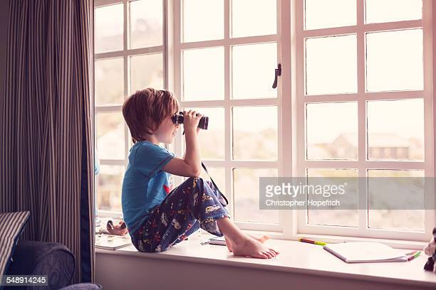 Boy on a window seat looking through binoculars