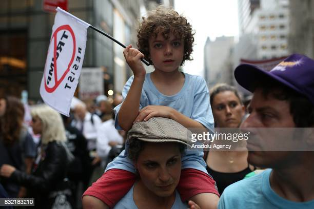 A boy on a woman's shoulders holds a banner reading 'Resist Trump' during a rally against US President Donald J Trump's potential repealing of...