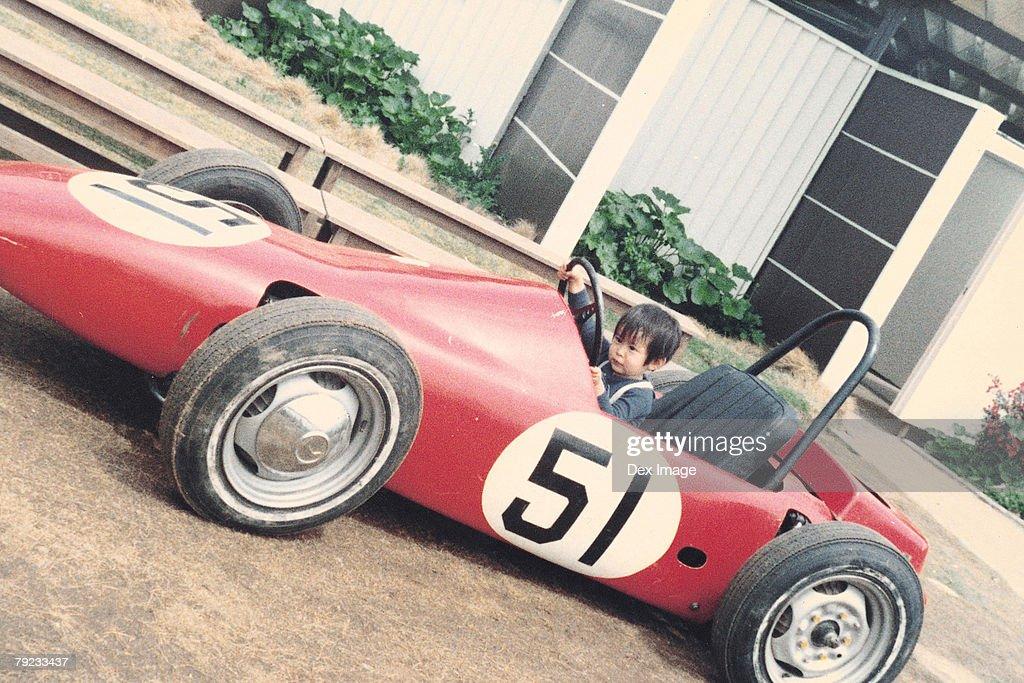 Boy on amusement racing car ride : Stock Photo