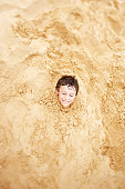Boy on Beach Buried to his Neck in Sand