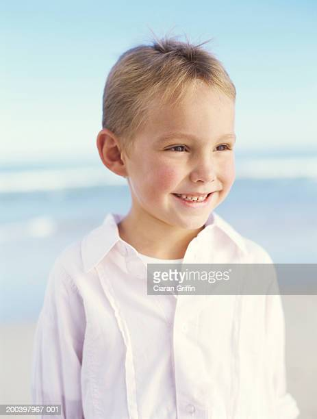 Boy (5-7) on beach , close up, smiling