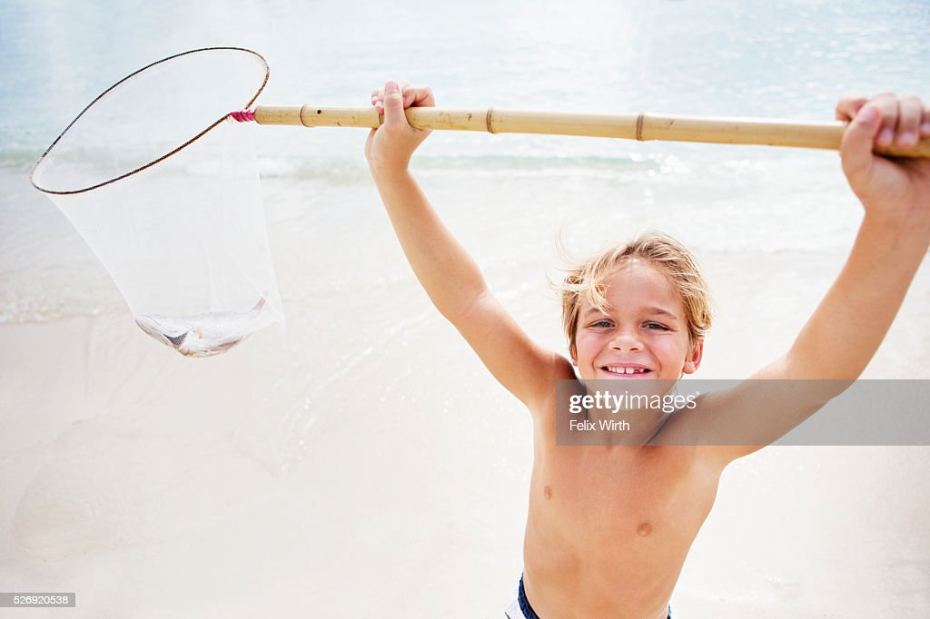 Boy (8-9) on beach lifting fishing net : Stock-Foto