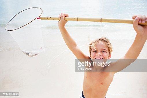 Boy (8-9) on beach lifting fishing net : Stock Photo
