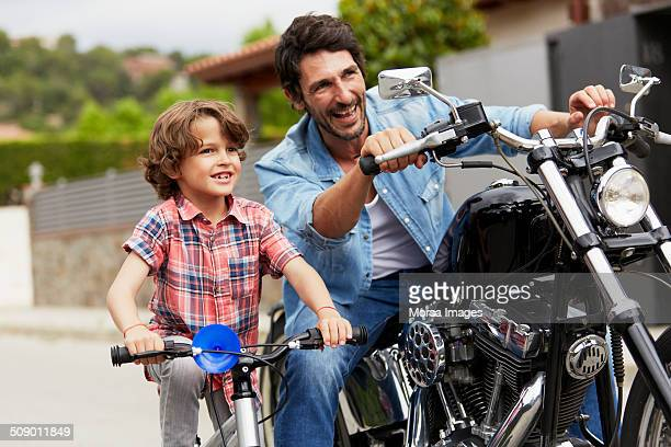 Boy on bicycle by father riding motorbike