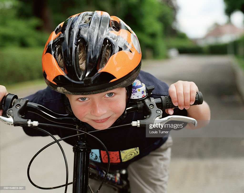 Boy (6-8) on bicycle, leaning forward, portrait, close-up : Stock Photo
