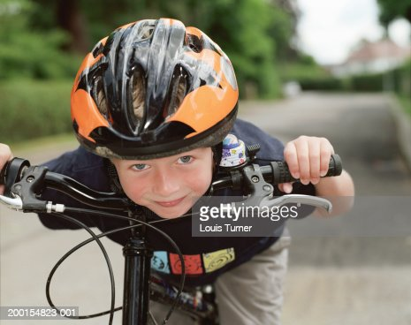 Boy (6-8) on bicycle, leaning forward, portrait, close-up : ストックフォト