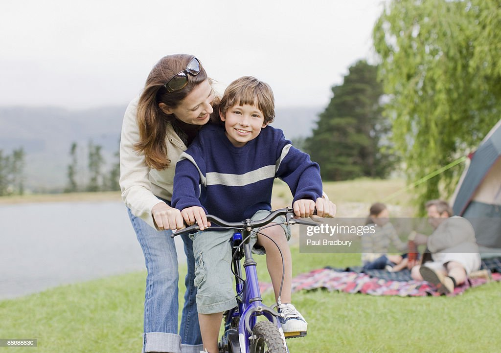 Boy on bicycle while on family camping trip : Stock Photo