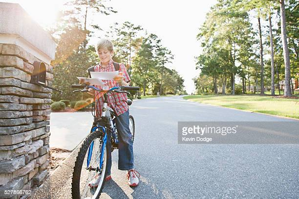 Boy (10-12) on bike standing by mailbox and reading letter