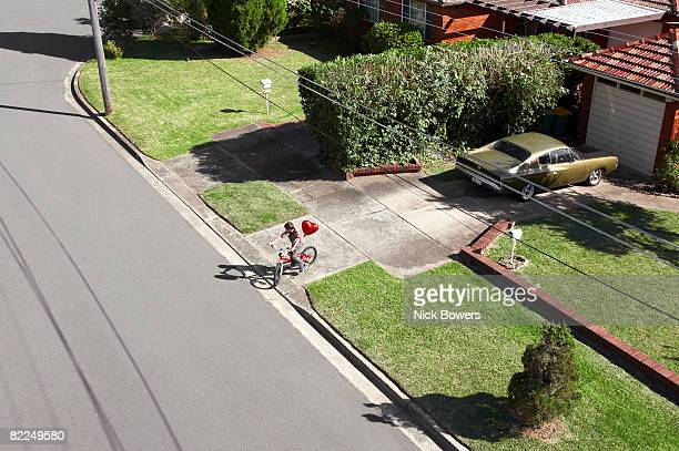 Boy on bike with red heart shaped balloon