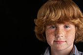 Boy (10-12) on black background, portrait, close-up