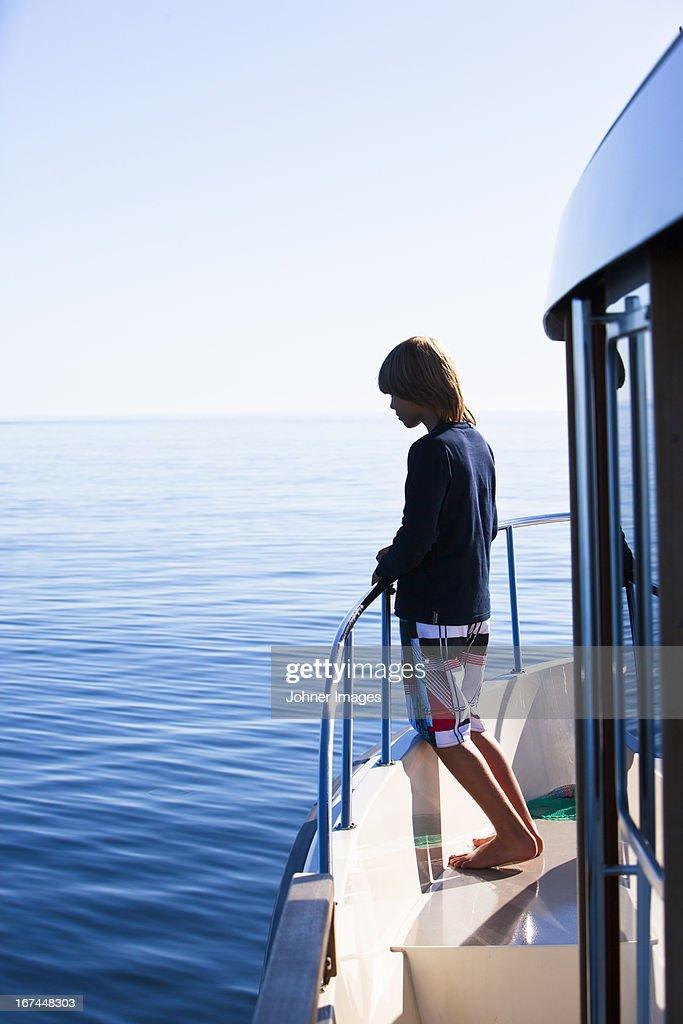 Boy on boat looking away : Stock Photo