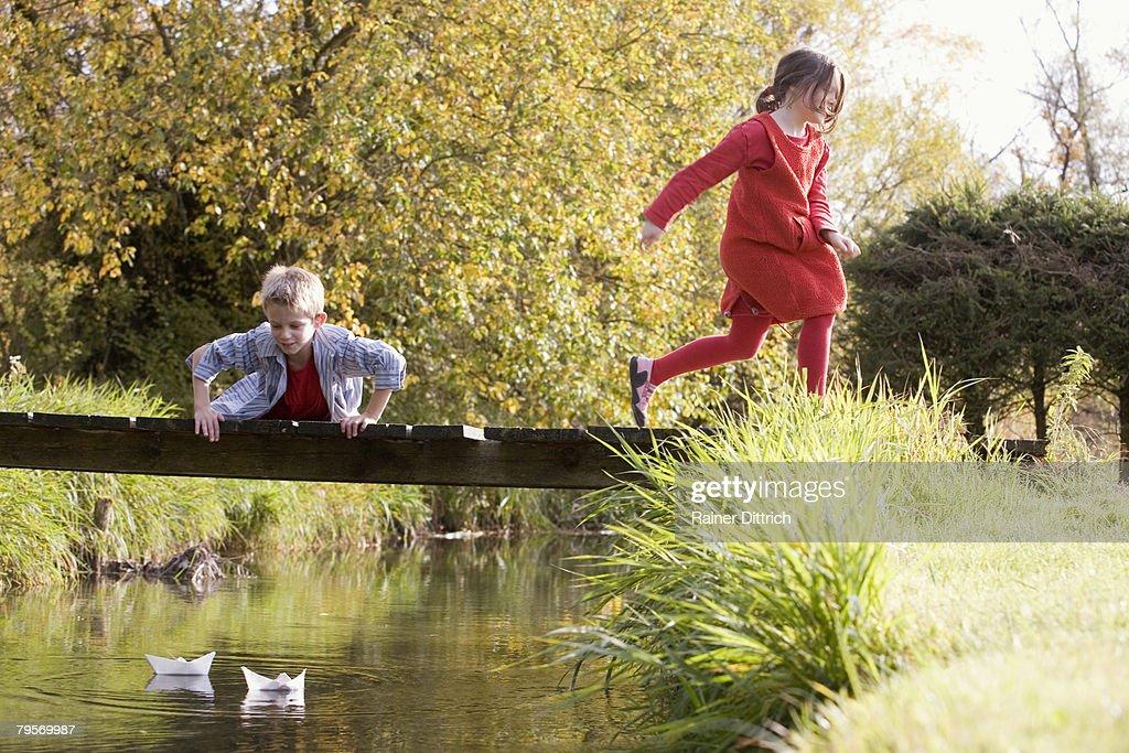 'Boy (10-12) on bridge, girl (7-9) running away' : Stock Photo
