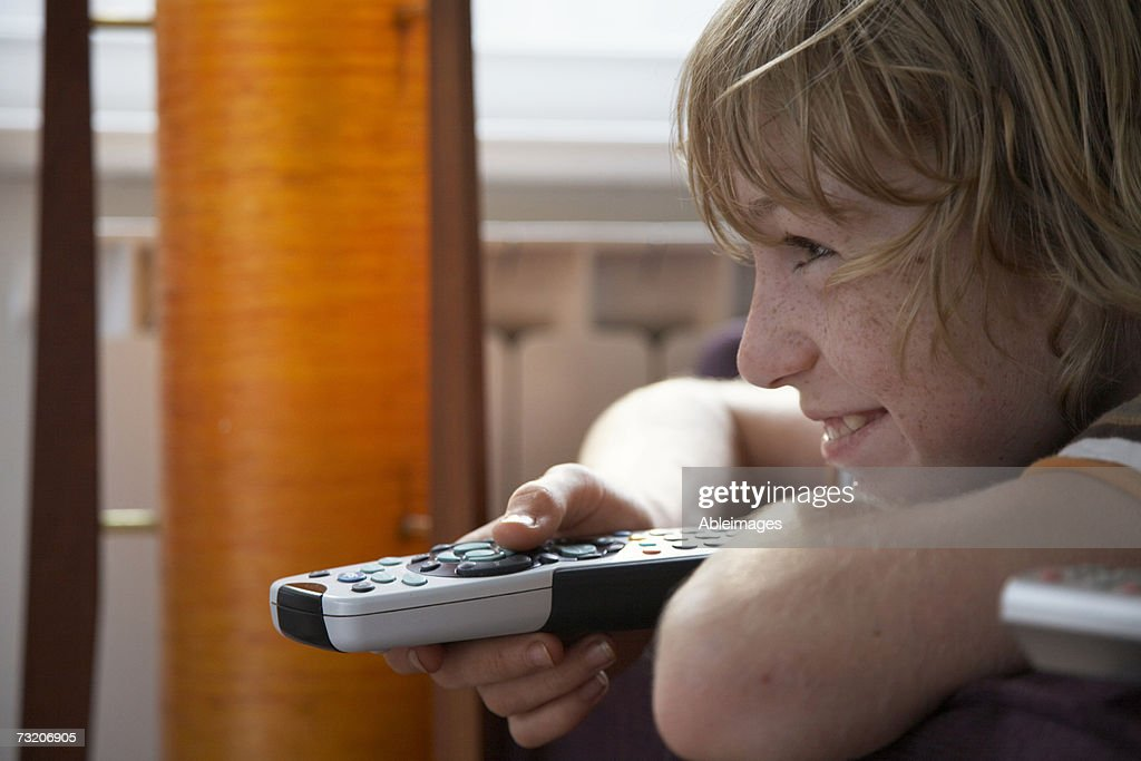 Boy (11-13) on couch, watching television : Stock Photo