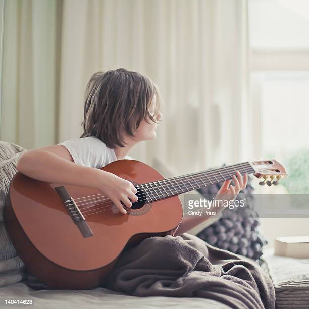 Boy on couch with blanket and his guitar