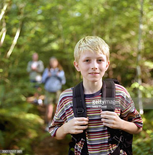 Boy (8-10) on hike, wearing backpack, portrait