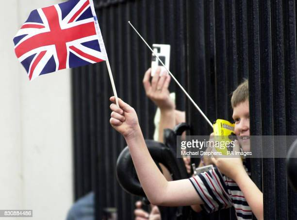 A boy on his radio listening to the World Cup game between England and Denmark whilst waving the Union Jack through the gates during the Trooping The...