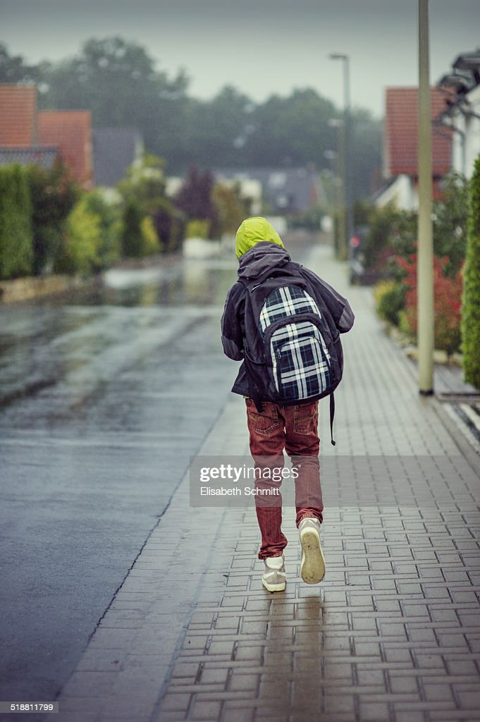Boy on his way to school on a rainy day