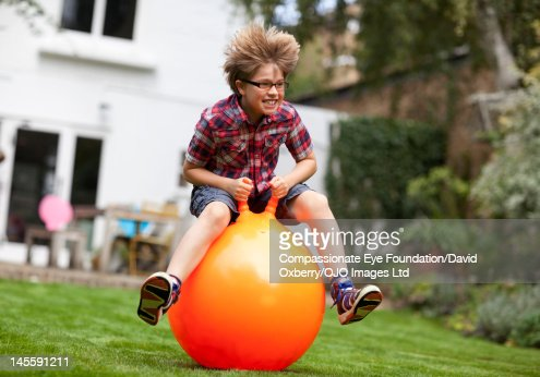 Boy (8-9) on inflatable hopper in garden : Stock Photo