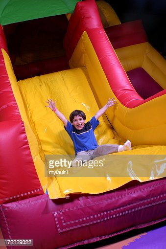 Boy on inflatable slide goes fast