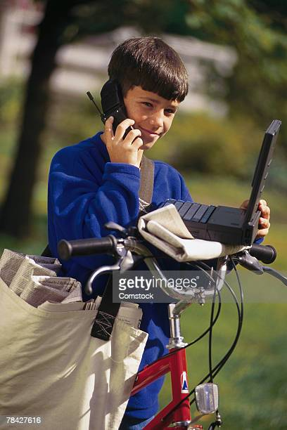 Boy on newspaper route with laptop and cell phone