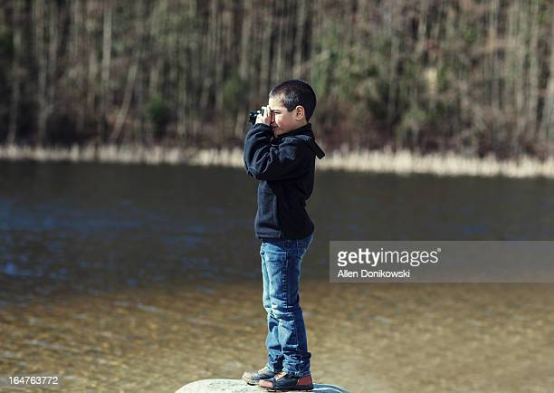 boy on rock taking picture at lake with camera