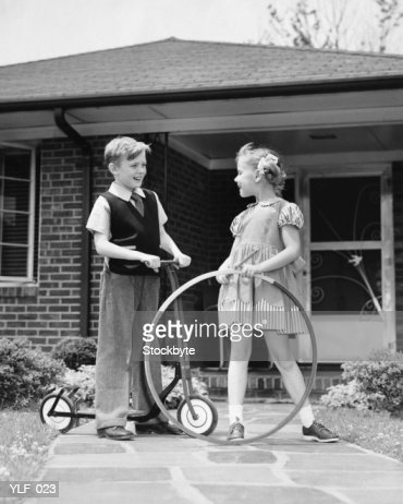 Boy on scooter, girl holding stick and hoop, outdoors