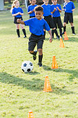 A 7 year old African-American boy on a soccer team at practicing, kicking a ball around cones. Other children are waiting their turn to do the drill.