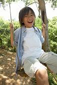 Boy (8-9) on swing, laughing, portrait