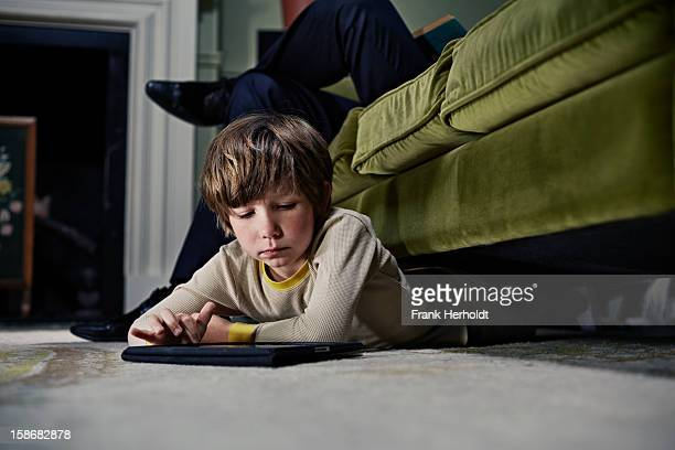 Boy on tablet computer under sofa
