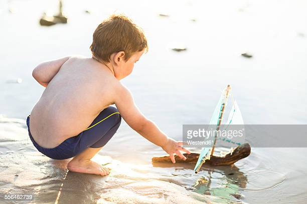 Boy on the beach playing with a toy wooden boat in the water