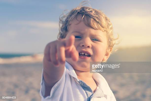 Boy on the beach pointing finger to a camera