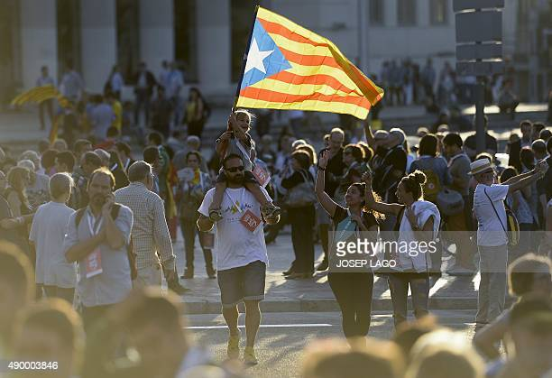 A boy on the sholders of a man waves a 'Estellada' Catalan independentist flag during the Catalan independence coalition 'Junts pel Si' party's final...