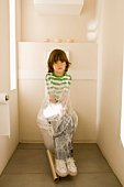 Boy on toilet wrapped in plastic wrap