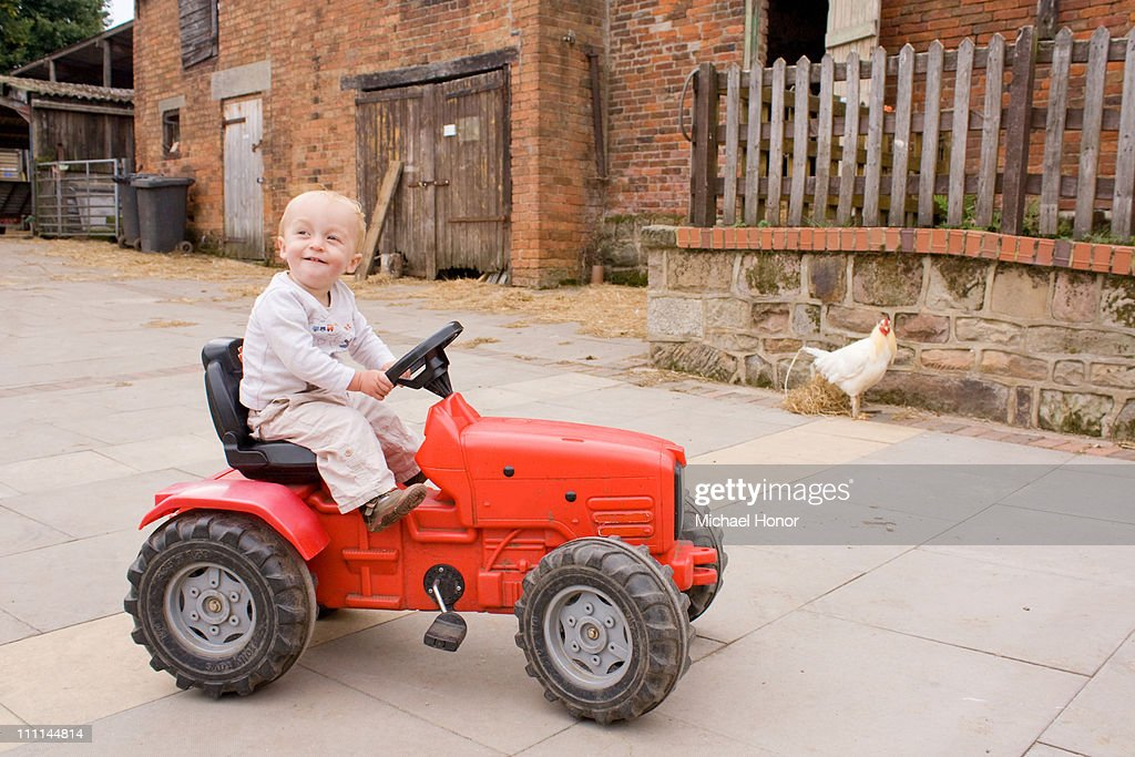 Boy On Tractor : Boy on toy tractor in farmyard stock photo getty images