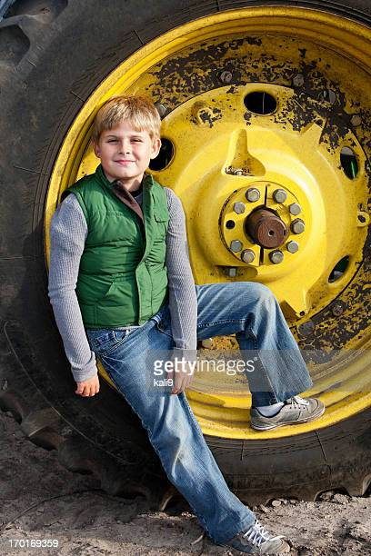 Boy on tractor wheel