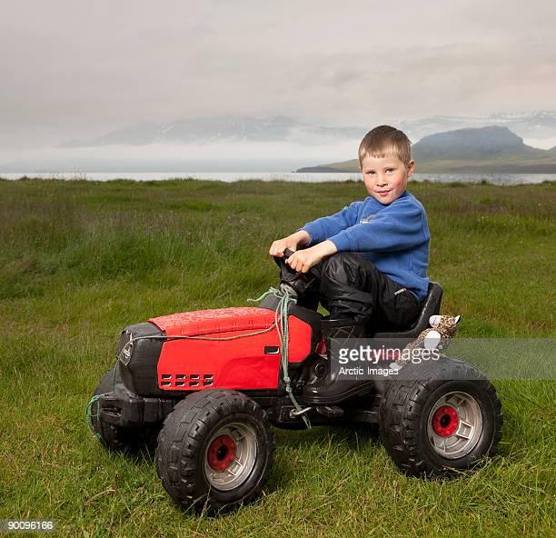Boy on Tractor with stuffed animal