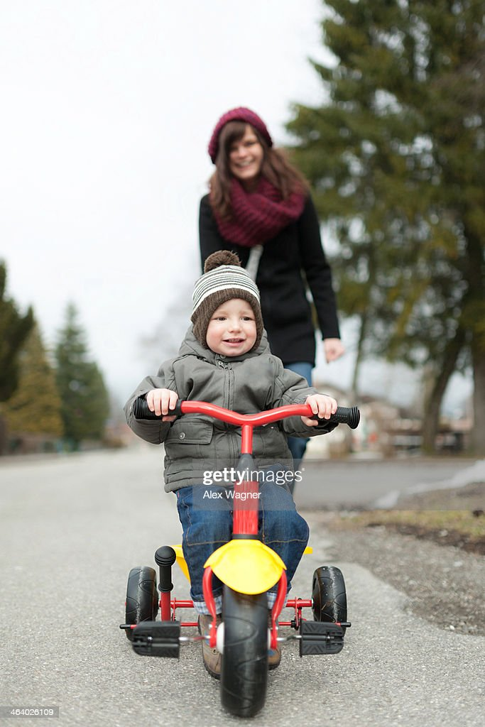 Boy on tricycle with mother in background : Stock Photo