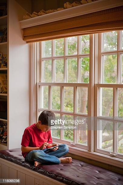 boy on window seat exploring a cell phone