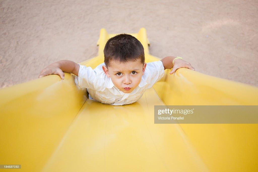 Boy on yellow slide : Stock Photo
