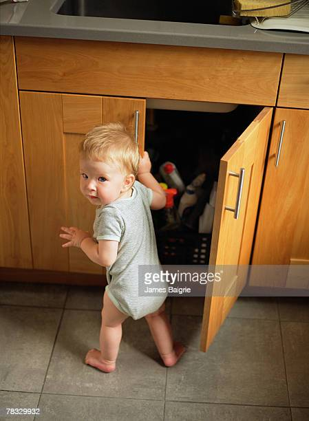 Boy opening a kitchen cabinet