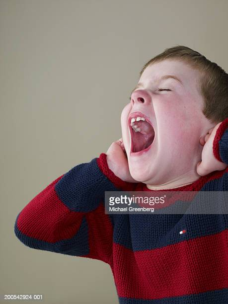 Boy (4-6) opening mouth wide, covering ears