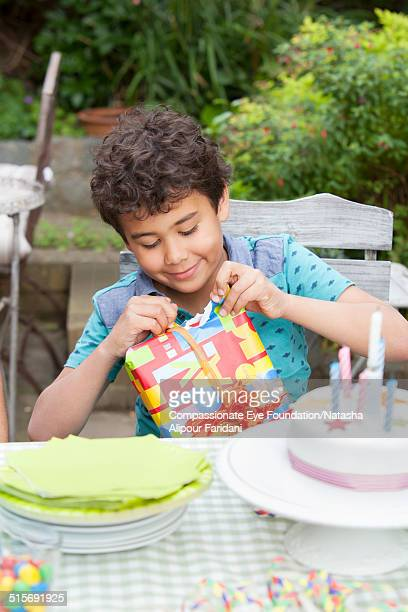 Boy opening present at birthday party