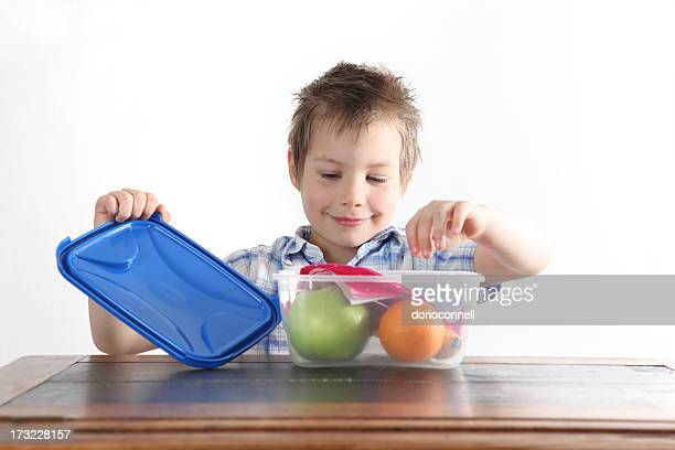 A boy opens a Tupperware box with an apple and orange inside