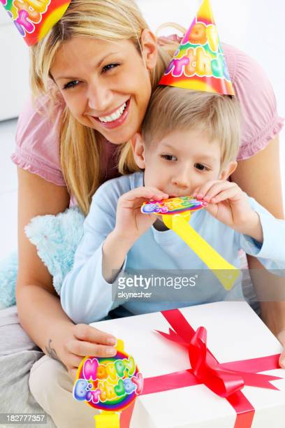 Boy opens gifts in the arms of his mother.