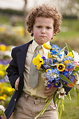 Boy outdoors carrying bouquet of flowers