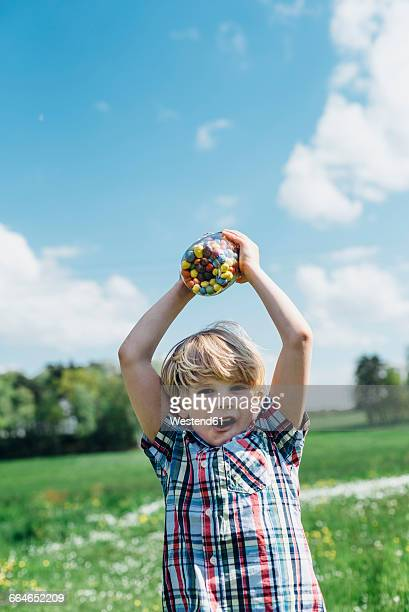 Boy outdoors holding glass with jelly beans