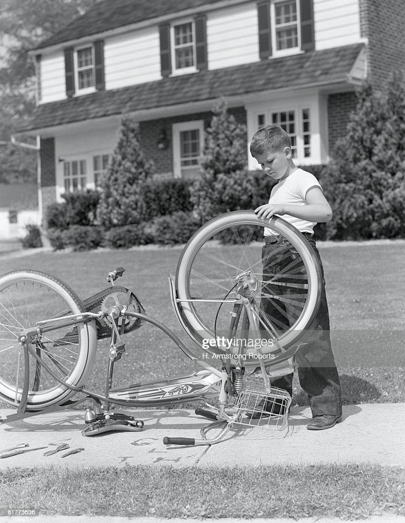 Boy outside front of house, bicycle upside down, spinning front wheel. : Stock Photo