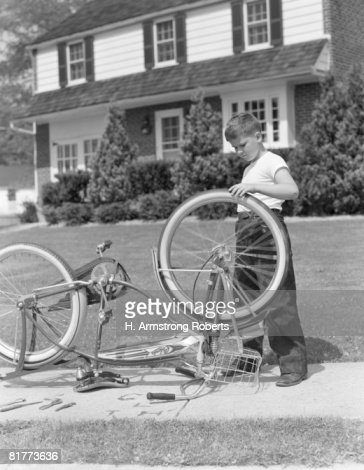 Boy outside front of house, bicycle upside down, spinning front wheel. : Photo