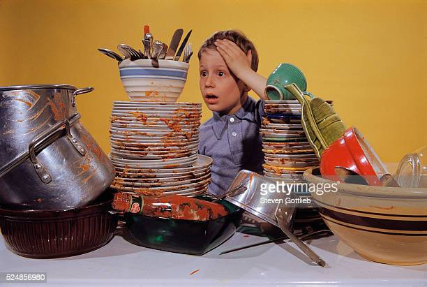 Boy Overwhelmed by Dirty Dishes